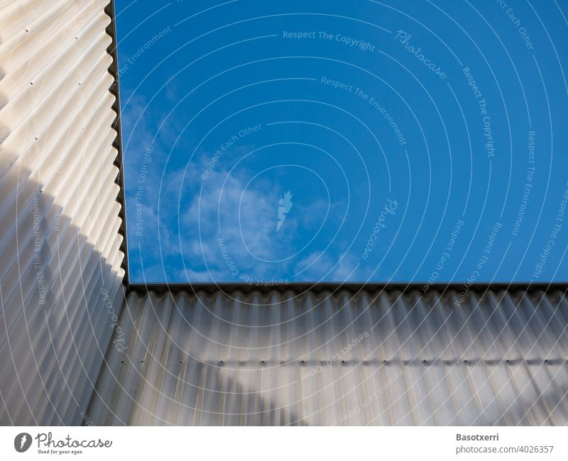 View of the blue sky on a modern semi-transparent corrugated facade Facade Plastic crimped semitransparent Transparent sunny Blue sky Light Shadow Modern nobody