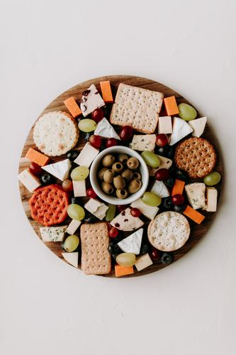 Cheese platter with different type of cheese. Camembert, cheddar, goat chesse, bleu, grapes and olive with crackers. Healthy vegetarian food idea. flat lay