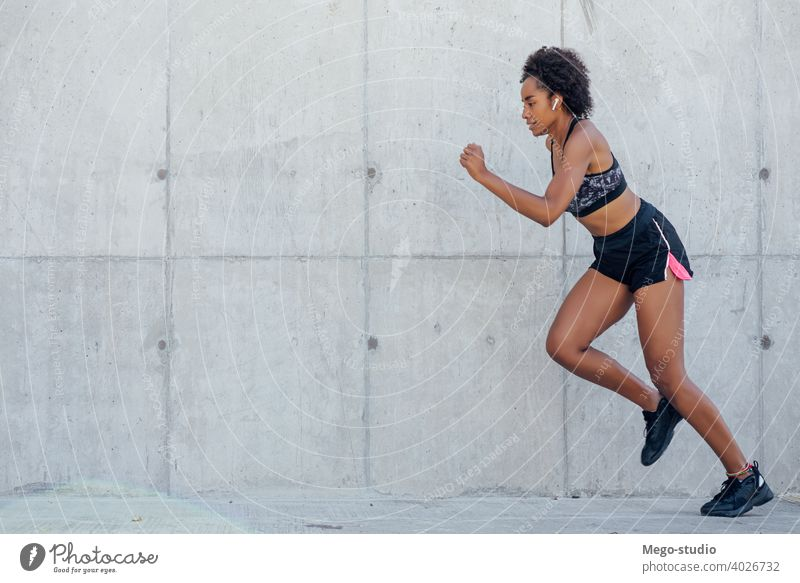 Afro athletic woman running outdoors. sport exercise training runner background people care leisure body portrait sports action motion cardio exercising