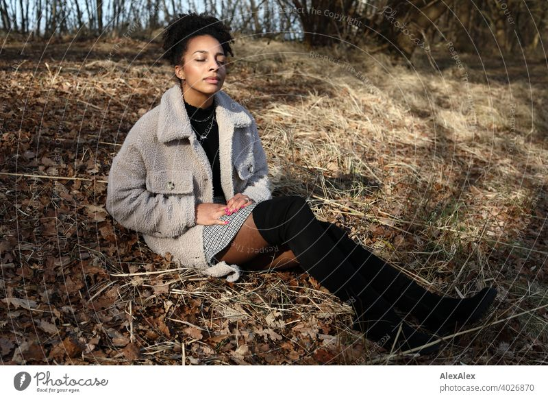 Young woman in fur jacket and skirt sits in nature sunbathing Woman Athletic Dark-haired Long-haired pretty Strong Graceful naturally Curly Slim Nature by