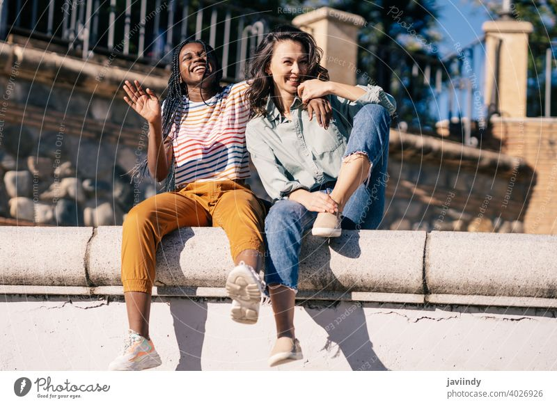 Two friends having fun together on the street sitting on a urban wall. women multiethnic black afro girl student two people lifestyle smile female pretty young