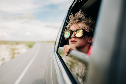 A boy looks out of a window of a moving vehicle with kaleidoscope glasses on Kaleidoscope kaleidoscope goggles road trip Vacation & Travel Vacation mood child