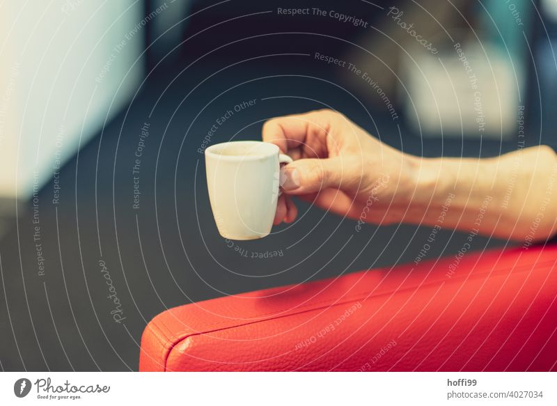 Espresso cup in hand with red armrest Cup Hand Crockery Red red sofa Morning Caffeine esspresso Black Breakfast Hot drink Café To have a coffee To enjoy