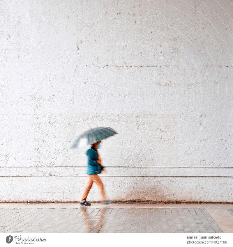 woman with an umbrella in rainy days in spring season people person raining water human pedestrian street city urban bilbao spain walking lifestyle weather