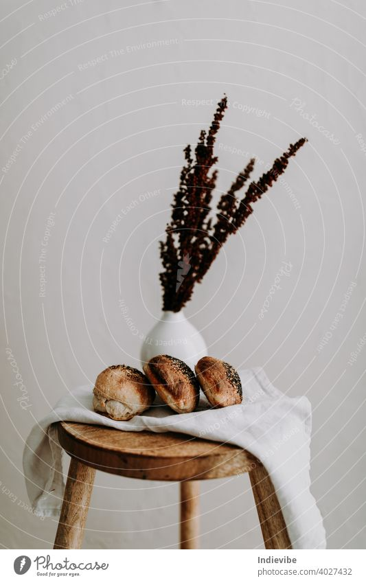 Three sourdough bun with poppy seed and sesame on a napkin on a wooden stool, and dried wild flower at the background breakfast bread gluten bread roll pastry