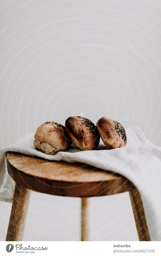 Three sourdough bun with poppy seed and sesame on a napkin on a wooden stool breakfast bread gluten bread roll pastry bakery fresh morning flour whole meal food