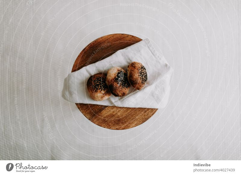 Three sourdough bun flat lay with poppy seed and sesame on a napkin on a wooden stool breakfast bread gluten bread roll pastry bakery fresh morning flour whole