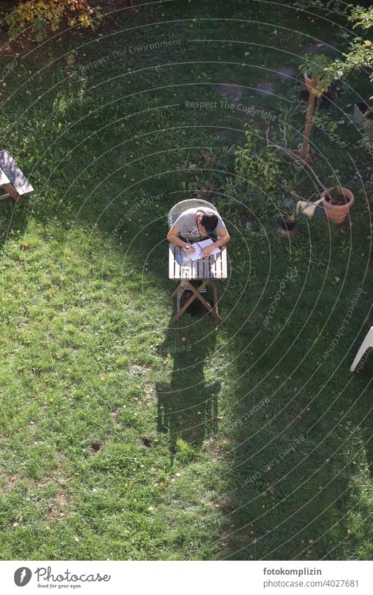 Bird's eye view of a young man sitting at a small table in the garden and writing in a notebook. Young man Garden table Study study Write Workplace