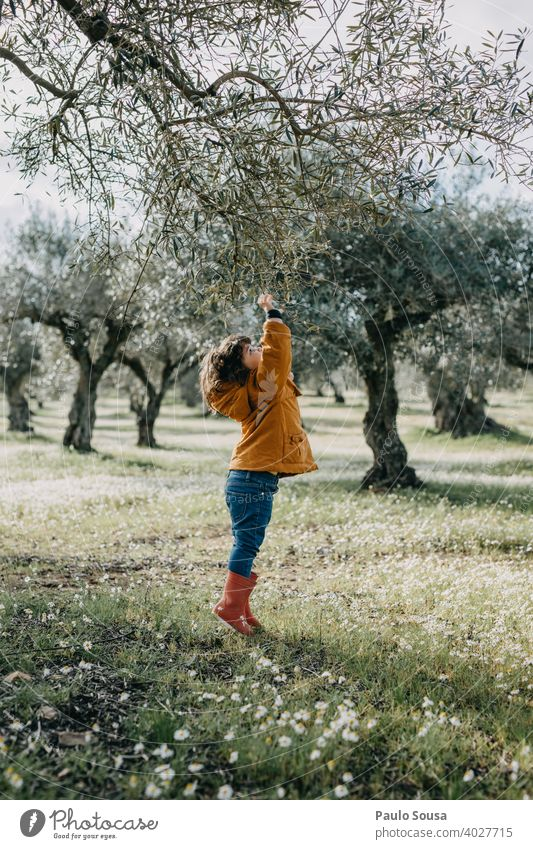 Child with red rubber boots playing with tree Tree Environment Nature childhood Spring girl Day green Infancy spring Colour photo nature kid Exterior shot