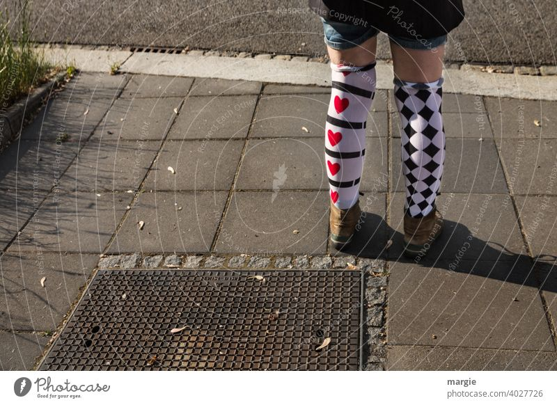 AST10 l A girl wears two differently patterned stockings with red hearts and black checks Stockings Heart diamonds Pattern pattern mix short pants Footwear