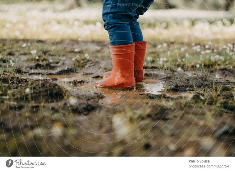 Child with red rubber boots playing on a puddle Puddle Red Rubber Rubber boots childhood Weather Human being Water Playing Infancy Boots Joy Wet Rain Authentic
