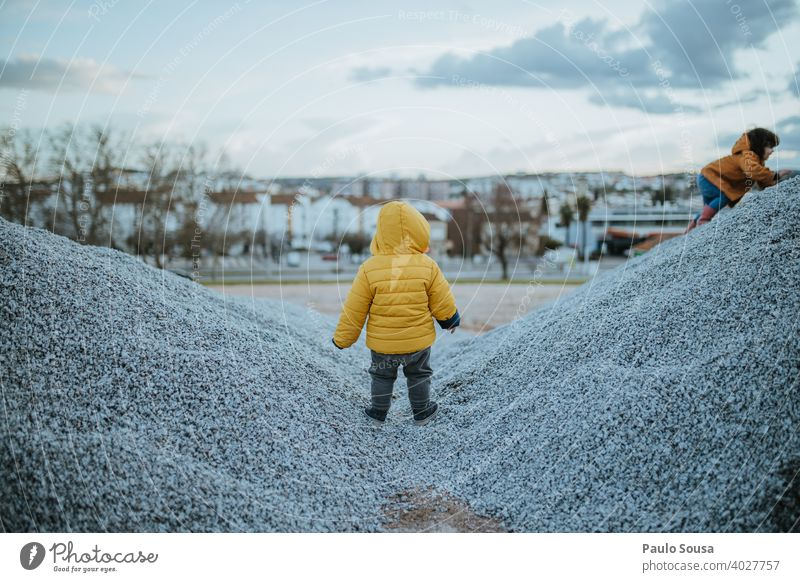Rear view child playing outdoors Brothers and sisters Child childhood Playing Unrecognizable Yellow Winter Lifestyle Leisure and hobbies Toddler Exterior shot