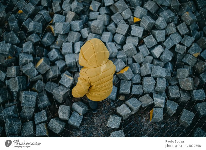 Toddler playing with rocks explore Yellow Child Rear view Infancy Exterior shot Nature Colour photo Leisure and hobbies Adventure Day Human being Boy (child)