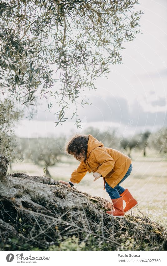 Child with red rubber boots climbing Climbing Red Rubber boots outdoors Nature Spring explore Adventure Exterior shot Playing Human being Rain Infancy Joy Boots