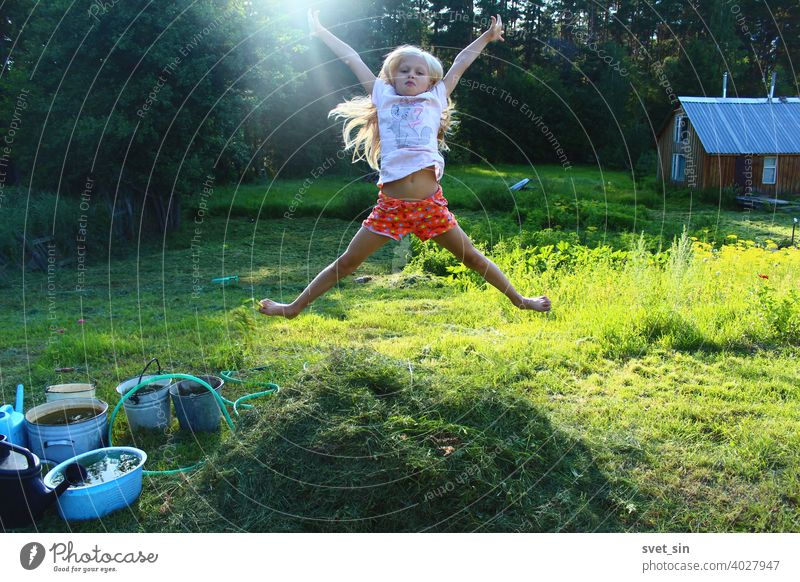 Barefoot childhood in the village. Portrait of a little blonde girl jumping in the air over a small stack of freshly cut grass on a green sunny lawn against the backdrop of a forest and a wooden bathhouse.