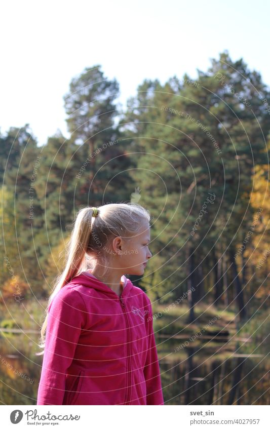 A teenage girl with long blond hair stands on the shore of a lake against the backdrop of water and autumn yellow forest in autumn sunlight. Portrait of a blond girl in profile.