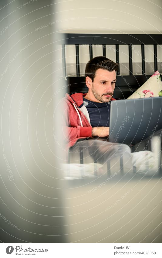 Man on laptop in bed labour Bed Notebook Internet free time Surfing home office Comfortable Easygoing Online Lie