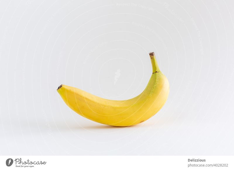 A single banana on a white background, with copy space abstract appetizing banana yellow calcium concept dessert diet eat eating energy food food and drink