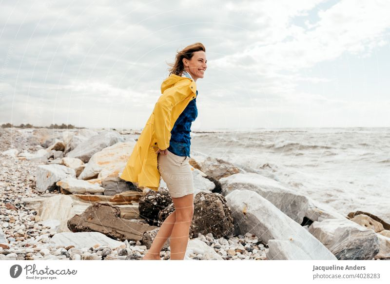 Woman with blowing hair in a yellow raincoat looks at the sea Ocean Seashore Wind Raincoat Yellow hair in the wind fortunate Summer Nature Freedom