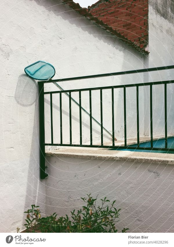 Pool landing net leaning against an iron railing next to a swimming pool in the backyard Landing net Backyard Swimming pool Wall (barrier) brick Wall (building)