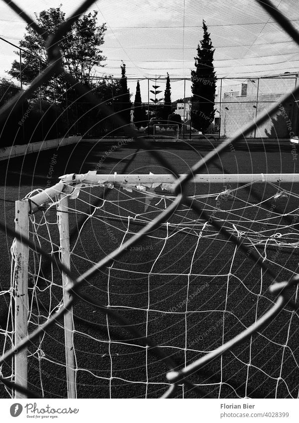 View through a fence onto an open sports field with opposing soccer goals spectators Insight Hard court Coating Playing field parameters training ground