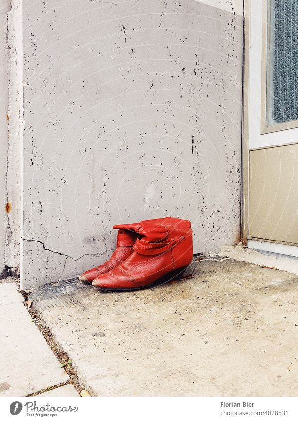 A pair of red lady's boots to be given away and no longer worn, parked in front of a house entrance. Red Footwear Boots High heels bootees Leather shoes Carried