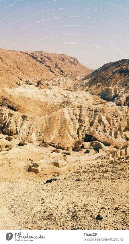 Beautiful landscape of Israeli Judean Desert mountains, with dry riverbed, popular hiking trail winding between rugged rocky cliffs towards the Dead Sea israel