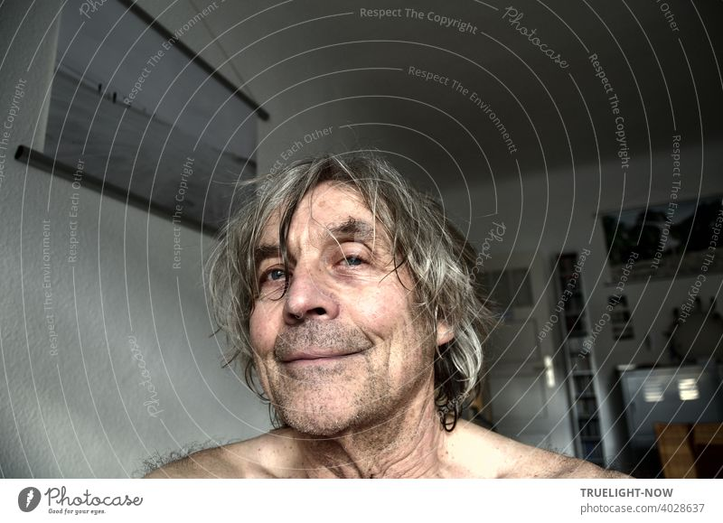 Frontal portrait of a senior citizen in his home office, who seems pleased that he hasn't been able to visit the hairdresser in over a year because of the pandemic. On the wall a photo of the Photocase user CL