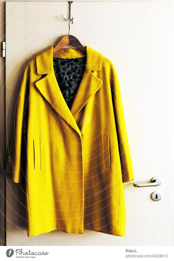 A coat hangs on the hook Coat Interior shot Transition coat door door handle Hanger Yellow Fashion conspicuous Neon yellow Summer coat