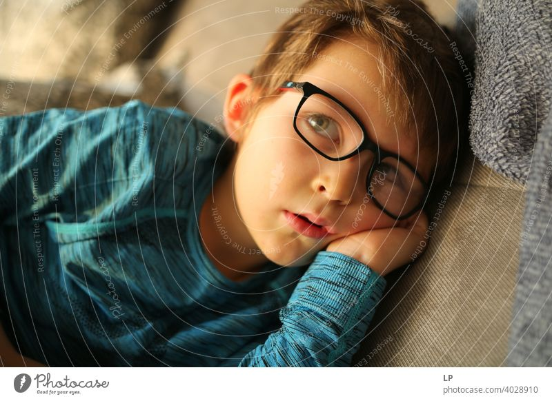 beautiful child wearing glasses looking very serious away from the camera puzzled Perplexed sceptical scepticism doubts Doubt hestitate uncertainty confusion