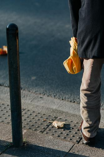 At the roadside Man Street Bollard person Pouch Bag Yellow leg Pants Jacket off corduroy trousers Stand Exterior shot Colour photo Human being Anonymous
