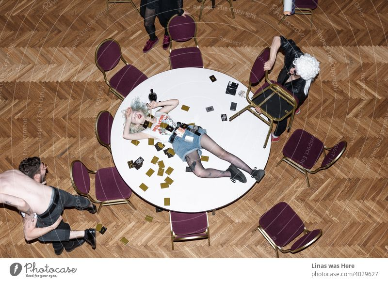 The kids are all wild. Making chaos during a card game. Fighting, drinking, laughing, wearing wigs, taking off the clothes, throwing chairs, lying on the table. You name it.