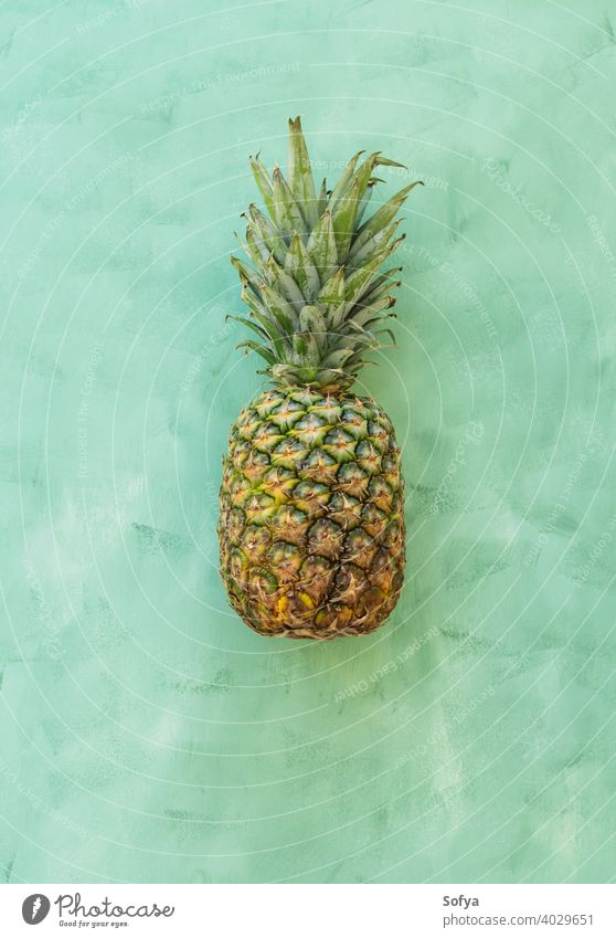 Whole pineaple fruit on green background, top view pineapple ananas ripe fresh summer organic texture close yellow group stem sweet delicious food healthy whole