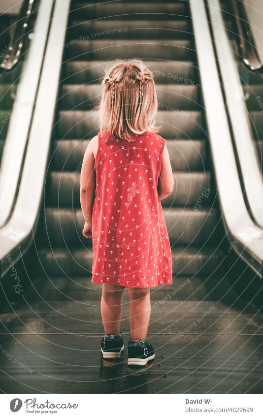 Girl in mind stands in front of an escalator Dress Escalator thoughts Shopping Shopping malls by oneself Child peril Doomed anxiously Shopping center Fear