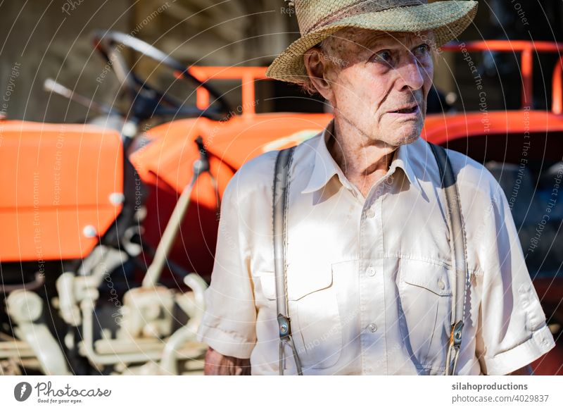 Portrait of very old farmer with straw hat explaining life in front of a red tractor. generation adult aged agriculture auto automobile car caucasian characters