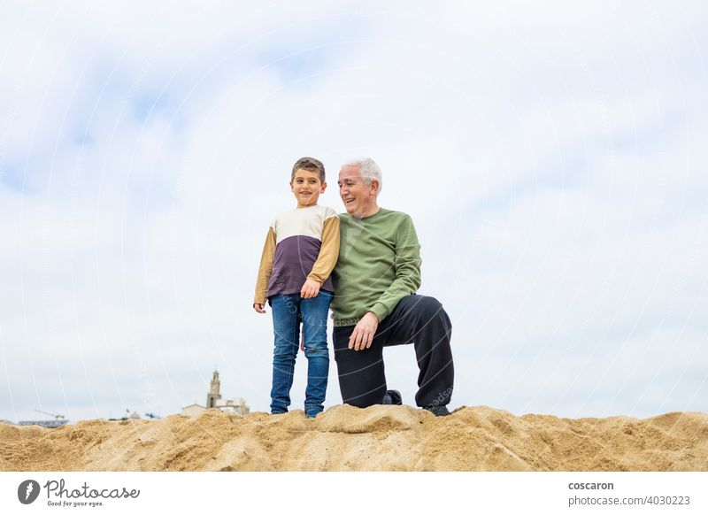 Little boy and his grandfather spending time on the beach baby beautiful cheerful child coast cute enjoying family fun generations girl grandchild grandparent