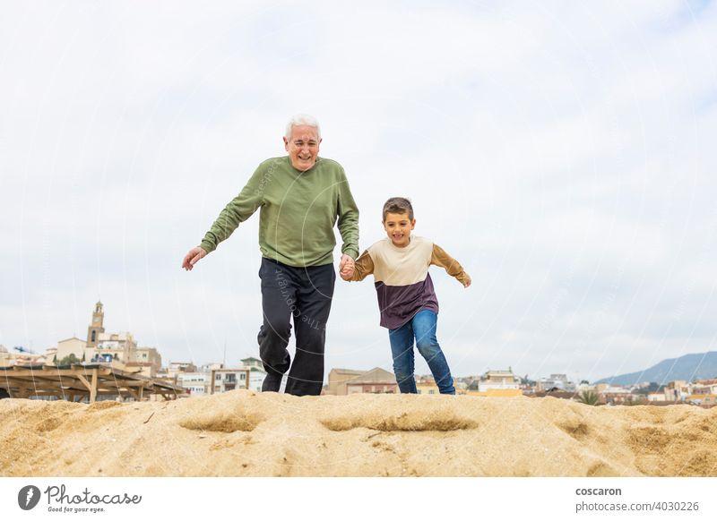 Little boy and his grandfather running on the beach active adult caucasian child childhood children elderly enjoying family generations grandchild grandchildren