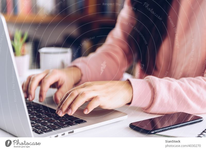 Young woman working at laptop on white marble desk at her home. young person hand table female library wooden coffee mug pen business background morning girl