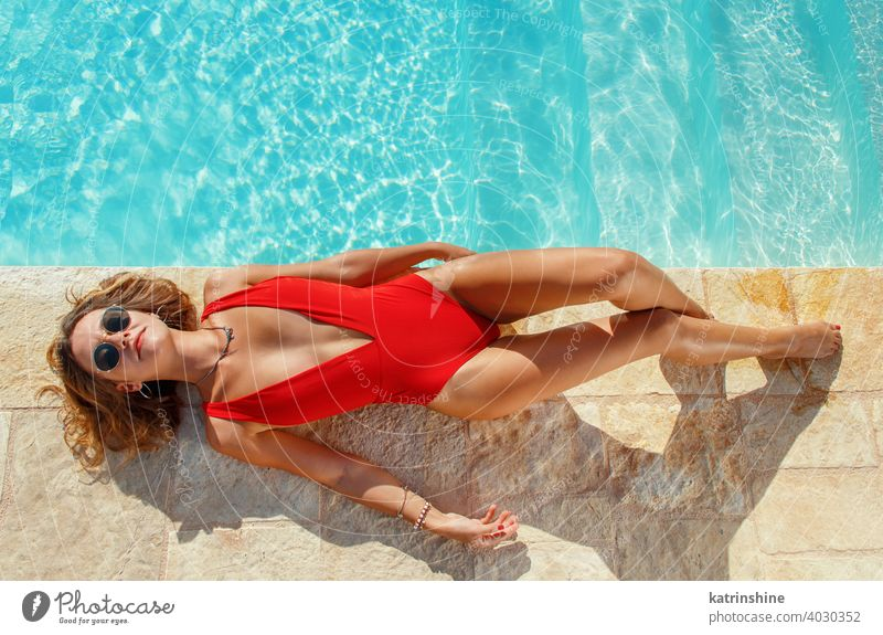 Young woman in red swimsuit relaxing near a pool tropical water one-piece copy space boho lay top view Summer caucasian Fashion alone Happy smile Garden Emotion