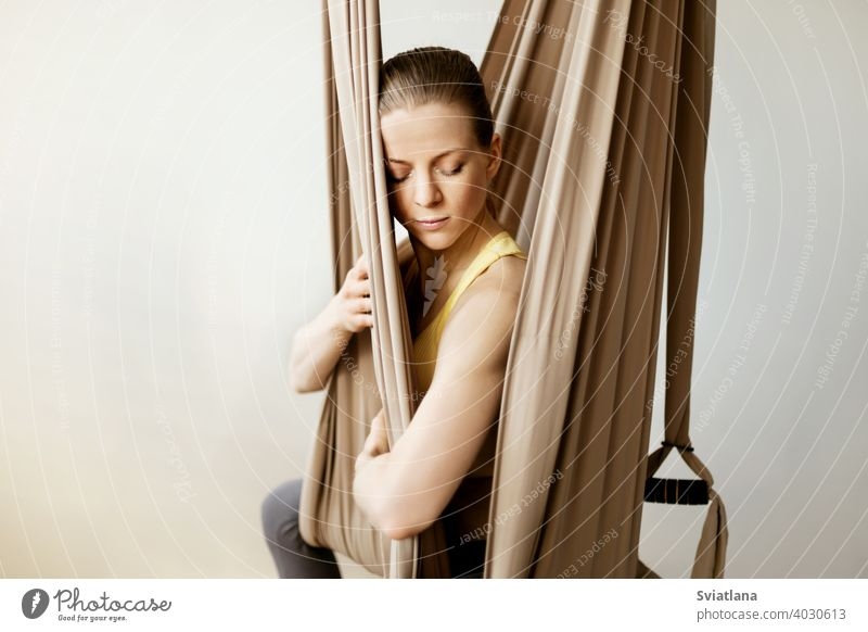 A young woman meditates while sitting in a hammock in a yoga class. Aero yoga, sports, healthy lifestyle fitness relax girl club meditation stretch pose aerial