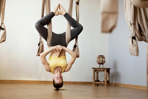 Sports girl is engaged in Aero yoga and performs asanas with the help of the hammock. Yoga, fitness, sports exercise antigravity woman pose gym balance active