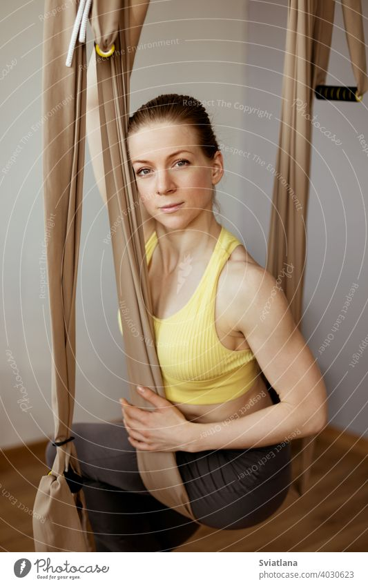 A young girl is relaxing after a yoga workout and sitting in a hammock for anti-gravity aerial yoga. Harmony, mindfulness and a healthy lifestyle fitness club