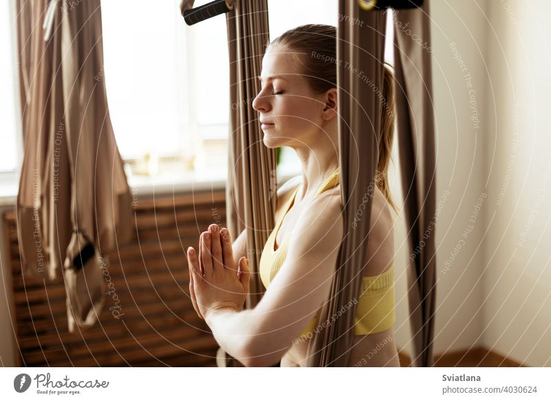 A young woman meditates in a hammock after an aero yoga class. Yoga-meditation in a hammock. Healthy lifestyle and relaxation concept fitness girl club stretch