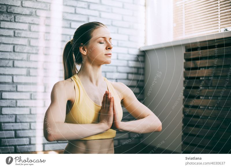 A blonde girl is resting after a fitness class and meditating. The concept of sports and a healthy lifestyle. Yoga, meditation young beautiful position lotus