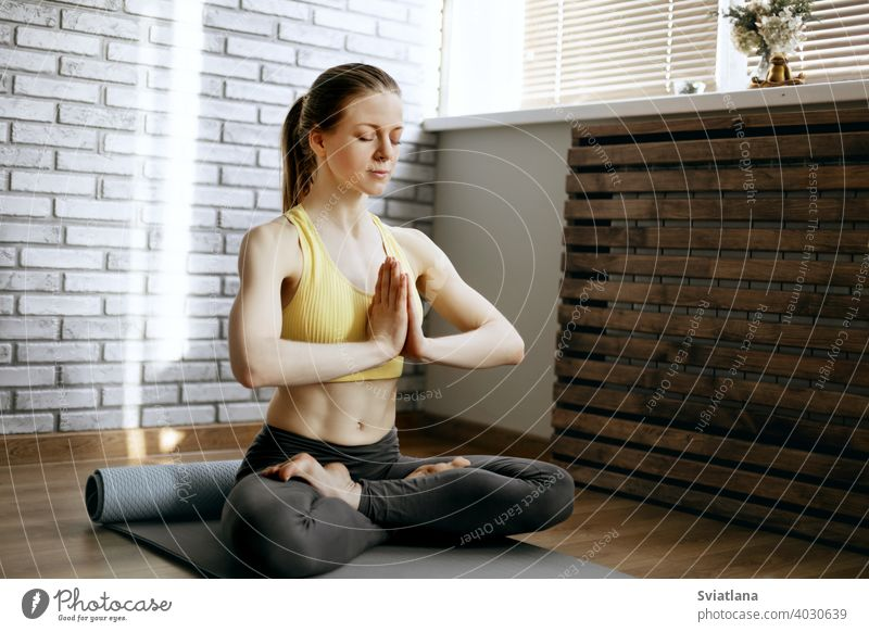 A beautiful girl sits in the lotus position and meditates. Yoga, fitness, meditation. Healthy Lifestyle Concept meditating young woman yoga lifestyle exercise