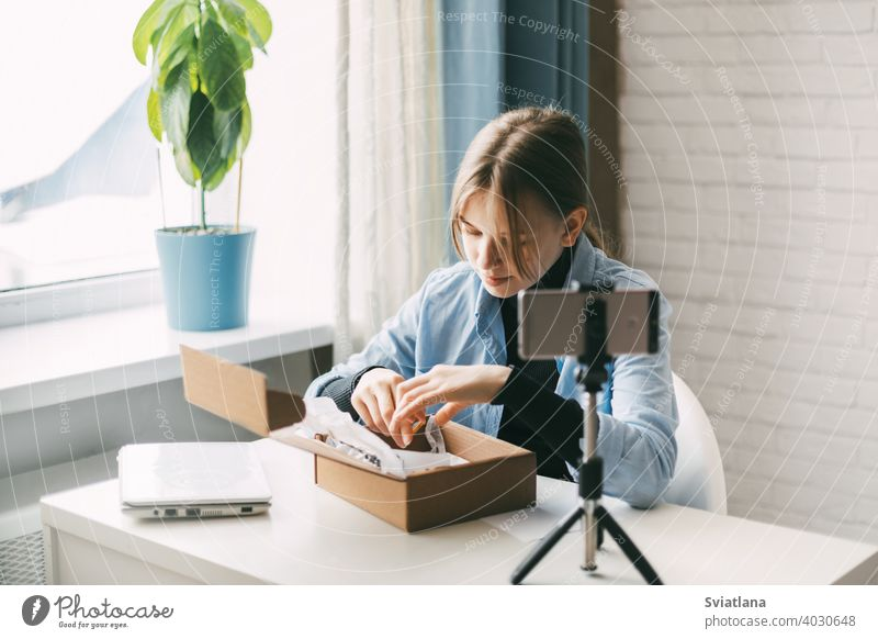 A teen blogger records a video and unpacks a package for his blog on a smartphone on a tripod at home. Communication of a video blogger girl on social networks with subscribers and friends.