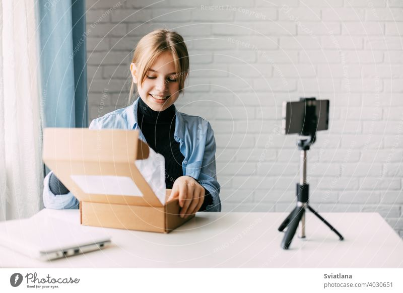 A teen blogger records a video and unpacks a box for his blog on a smartphone on a tripod at home. Communication of a video blogger girl on social networks with subscribers and friends