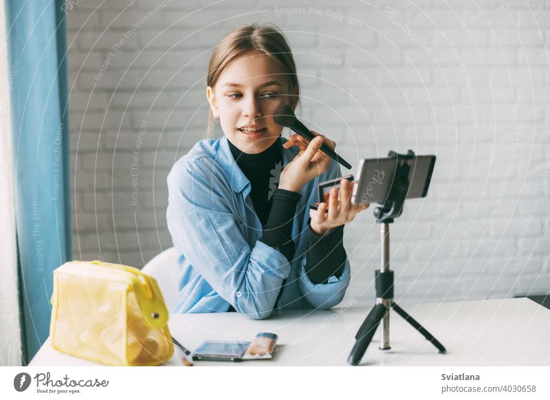 A teenage girl does makeup and records video for her blog on a smartphone on a tripod at home. Communication of a video blogger girl on social networks with subscribers and friends