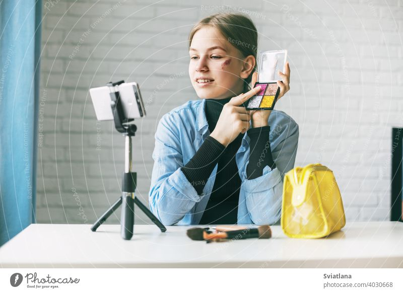 A teenage girl does makeup and shows how to apply blush while recording video for her blog on her smartphone on a tripod at home blogger camera cosmetics