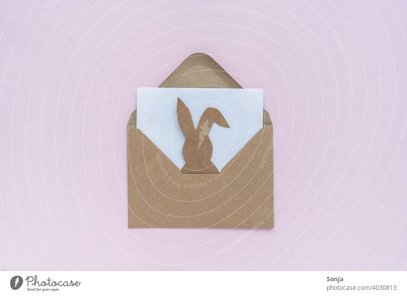 Brown envelope with a paper easter bunny on a pink background enveloped in a letter Open Easter Bunny Paper embassy message Hare & Rabbit & Bunny Funny Joy plan